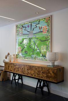 """O charme domina a sala da casa de praia Decortiles por Marina Linhares, dentro da exposição Casa Cor 2017. Cada peça nessa foto, é digna de nota. O lindíssimo aparador regulável Cacos da Etel, de madeira reaproveitada, que não leva prego e tem abertura intuitiva. O belo par de vasos Oceânico da Dpot Objetos. A encantadora luminária Behive, da Lumini, e a tela, colorida e feliz, """"Todos os caminhos"""", em tinta acrílica e colagens, da Galeria Fortes Vilaça, assinada pela Leda Catunda."""