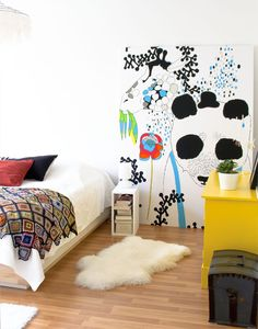 i like this idea of a large piece of art on the floor, with lots of white and a few super-bright color pops