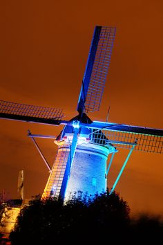 A windmill lit up with a eye-catching blue light at sunset......
