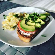 Whole wheat bread drizzled with olive oil then toasted served with goat cheese tomato and avocado slices with a side of scrambled eggs. [2048x1536]