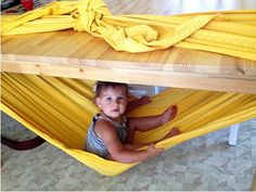 A baby hammock with a sheet and a table