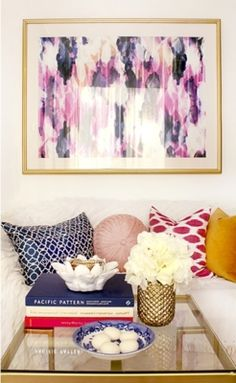 Love purple and gold for a living room. Touch of navy adds a masculine touch. Love the artwork, and the coffee table styling is very pretty.