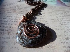 This necklace has a wonderfully coloured leopard jasper stone pendant that has been beautifully wire wrapped with copper wire. The copper wire wraps around the top and spirals down to sit upon the face of this pendant. The necklace is set upon antique copper chain and measures 25.5 inch's in length