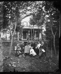 Family around table in yard with birch trees, and brick house with addition and shutters in background; porch has plants and two bird cages hanging from it. A stuffed owl sits on the table (c. 1869).