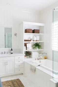 White shiplap bathroom featuring a dual washstand with a white and gray marble countertop, white framed mirrors and vertical shiplap walls. A white built-in shelf joins with a marble top bathtub trimmed with vertical shiplap bringing a cottage feel to the elegant bathroom design. Design Shop Interiors