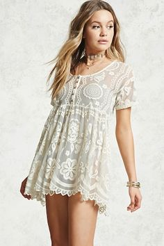 A babydoll dress featuring a sheer, embroidered lace construction, scoop neck, short sleeves, shirred waistline, and a five-button construction at the chest.