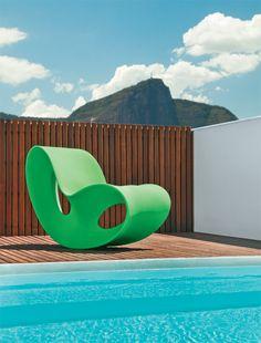 A poltrona de balanço verde Void, de polipropileto (Via Manzoni), destaca-se como uma escultura no deque.