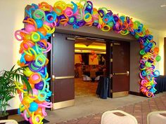 This design company decorates in unique and creative ways with balloons - from arches to walk throughs in the shape of a big gold and white star.  Love all the colors and shapes in this entryway.
