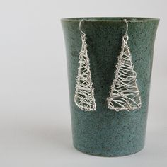 Silver wire wrapped dangle statement earrings, handmade by skilled artisans. The clean structure and contemporary feel make these bold earrings surprisingly easy to wear.