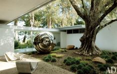 Turning the World Upside Down (1996) by Anish Kapoor stands in a courtyard. The 1954 Loop chairs are by Willy Guhl. / Singleton House designed by Richard Neutra.