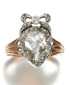 A DIAMOND RING, FIRST QUARTER OF 19TH CENTURY. Centring upon a pear-shaped diamond in a closed back setting, to a bow surmount set with single-cut diamonds.
