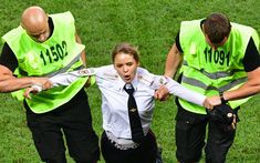 Veronica Nikulshina, a member of the Russian protest-art group Pussy Riot, is escorted off the pitch after staging an on-field protest during the Russia 2018 World Cup final football match between France and Croatia at the Luzhniki Stadium in Moscow on July 15, 2018. Photo by Mladen Antonov/AFP/Getty Images.