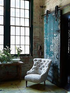 Warehouse home with exposed brickwork and painted salvaged barn door on industrial sliding rail