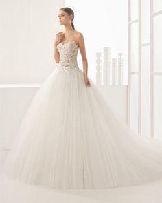 Vestido de novia princesa con cuerpo de encaje con transparencia y falda de tul de gran volumen, en color natural.
