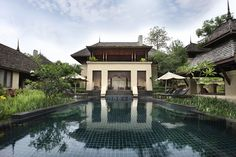 this Northern Thai luxury villa in Chiang Mai is inspired by traditional Thai architecture&located on a Four-Seasons resort surrounded by mountains and rice paddies-but only 30 mins from the airport... this photo shows a sunken dining pavilion that opens into a private heated lap pool and jacuzzi.  omg. the lush, tropical plants around this beautiful deep blue tiled pool makes it look and feel like you're swimming in your own private tropical lagoon. it's beautiful. $5,000,000