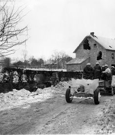 A 57-mm anti-tank gun of the 1st Infantry Division is towed through Steinbach, Belgium, in January 1945.