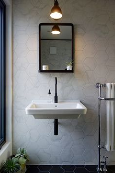 The loft bathroom by Making Spaces. With marble and black hex tiles, black tap, Lampe Gras 304 light and bathroom mirror with shelf.