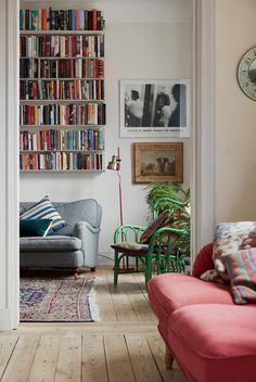 Wooden floor, red sofa, grey couch and white bookshelves full of colorful books.