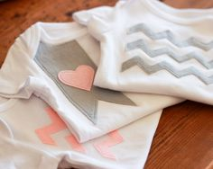 Baby shower idea - guests decorate onesies for mom-to-be. Chevron patterns - use fabric glue.
