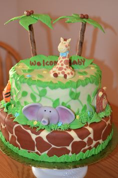 Jungle Baby Shower - Fondant animals and leaves. Palm tree's made from fondant and cookies. Girrafe print is also fondant. Top layer is vanilla bean cake with caramel sauce and caramel cream bottom layer is chocolate cake with raspberry preserves and raspberry cream. Italian Meringue Buttercream.