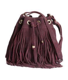 PREMIUM QUALITY. Een bucket bag van suède met franje. De tas heeft een verstelbare schouderriem, een drawstring aan de bovenkant en een binnenvak met ritssluiting. Gevoerd. Afmetingen 18x20 cm.