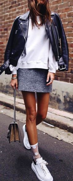 #spring #outfits woman in black leather zip-up jacket and white long-sleeved shirt with gray mini skirt walking while holding brown and gray shoulder bag during daytime. Pic by @milano_streetstyle