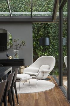 Womb Chair - Sofa and Ottoman -Designed by Eero Saarinen (1948). The white chair and rug create an inviting oasis in an open room.