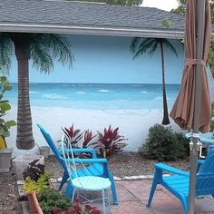 Patio faces a garage wall painted, planted to look like the beach w palm trees. What a relaxing improvement!