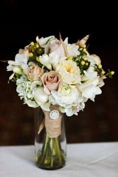 Beautiful bouquet of: ivory peonies, ranunculus, anemone, antique champagne garden roses, and ivory parrot tulips {winter wedding destination}