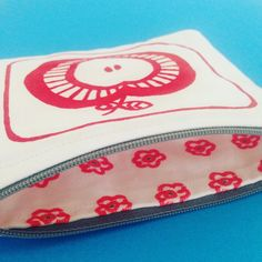 One of my handmade purses, with a red Scandi style screen printed apple design on the outside, and a hand drawn fabric pattern on the inside lining- cute mini flowers. I drew the flowers directly onto the cotton lining fabric, using a fabric pen. #pattern #patternmaking #patterndesign