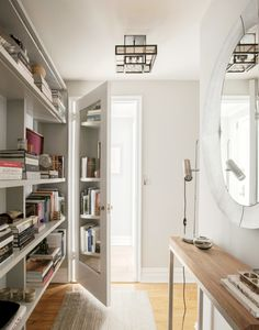 Entryway of library with console table and round mirror