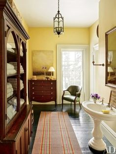 The master bath of architect Jim Joseph and musical theater composer Scott Frankel's upstate New York home is accented by a Tom Leaver painting and a wood chest of drawers and cabinet. The runner is an antique Venetian stripe | archdigest.com