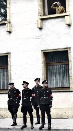 "Guardsmen of the SS-Allgemeine ""Leibstandarte"" division, the elite unit tasked with personally guarding the Führer with their lives, stands below the balcony where Hitler is actively conducting a speech. German Reich, 1934."