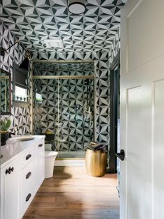 Tile takes center stage in this bath, the most dramatic space in the home. Geometric tile goes from floor to ceiling and doesn't stop there — it covers the ceiling, too! Innovative and luxurious features, from the toilet to the shower, elevate the guest bath to a spa retreat.