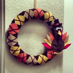Turkey Thanksgiving Wreath. Made this 9/29/13. Got a noodle from Home Depot for $.96. Bought sheets of felt for .30/each. I am not an artist by any means so I free handed the shapes for the turkey on a piece of paper until I got them right. Then safety pinned them to the felt to cut out. Then I hot glued them together.