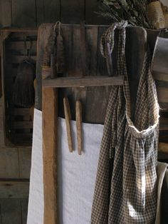 Early brown homespun apron, ironing board, hand carved clothespins and primitive candle holder.