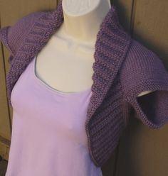 """The Dusty Plum Shrug vest will make a wonderful addition to any wardrobe, as a gift or for you. This shrug is knit in a medium worsted weight yarn, so it is a little heavier than most of my shrugs. It has garter stitch arm holes that cap the top of your shoulders. This item features a 4"""" moss ribbed edging that creates a collar, which extends around the torso, giving a body hugging effect. Perhaps it would make a good cover up for a strapless party dress? Size Medium, fits 40"""" to 42"""" Bust…"""