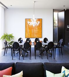 """Minotti """"Van Dyck"""" dining table from Dedece and Philippe Stark """"Ghost"""" chairs from Space. The chandelier is Murano crystal. Painting by Scott Petrie (Scottpetrieart.com)."""