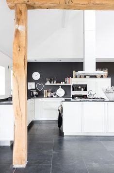 White kitchen, grey stone floor and wood beams