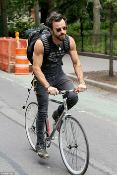 Pedal power: Justin Theroux showed off his bulging biceps in yet another tank top as he cycled through New York City on Saturday