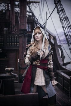 Female Steampunk Pirate - woman wearing hooded shirt, jacket, red sash, belt, knee socks and boots (lady pirate?) Edward Kenway - Assassin's Creed  - For costume tutorials, clothing guide, fashion inspiration photo gallery, calendar of Steampunk events, & more, visit SteampunkFashionGuide.com