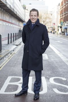 Wearing a Harrods overcoat, suit, scarf, shirt and tie with Prada shoes.