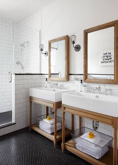 Shared kid's bathroom boasts weathered oak vanity mirror mounted on white walls accented with white subway backsplash tiles positioned behind side-by-side Restoration Hardware Weathered Oak Single Washstands placed on black hex floor tiles lit by industrial cage sconces.