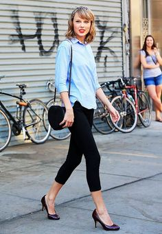 Taylor Swift wears a button-down shirt, cropped skinny pants, round-toe pumps, a round shoulder bag, and a scarf headband