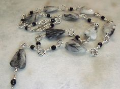Gotham Long Gemstone Necklace~ A dark, steely Gothic design, also described as somewhat Steampunk in its industrial coloring. Faceted tourmalated quartz nuggets with needles of black tourmaline, onyx and sterling accents. Thirty-inches long with a 3-3/4 inch long drop.
