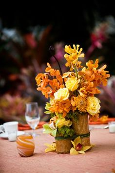 tropical arrangement of Mokara & Cymbidium orchids, pincushion Protea, Roses and Lily grass in clustered bamboo stems Bamboo Centerpieces, Tropical Wedding Centerpieces, Flower Centerpieces, Wedding Reception Tables, Reception Ideas, Reception Decorations, Flower Arrangement Designs, Flower Arrangements, Wedding Bouquets