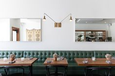 Commercial banquette seating.  Love the green leather upholstery, white walls, wood table tops, black cane chairs, warm brass swing arm lighting.  Simplistic and gorgeous.