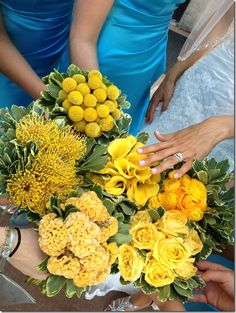 I grabbed this picture because you can see the yellow roses, billy balls, and callas close together which is what your bridesmaid currently have.  If you want to add a hint of white I would suggest freesia, or white spray roses.  They are inexpensive and hardy enough to withstand the heat.
