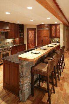 Isla formada por la pared de piedra y paneles de madera rica a juego con los gabinetes a lo largo de esta cocina, cuenta con encimera de mármol y se crió superficie de comedor de madera. #cocinaspequeñasconbarra