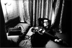 "Elvis Costello by Anton Corbijn Amsterdam, 1977 Taken in the smallest of hotelrooms in Amsterdam when Elvis came to Holland to promote "" My Aim is True "". Although I rarely shot musicians with their instruments, with Elvis it seemed very natural and it is one of my strongest photographs of my years in Holland as a photographer."